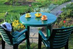 Les meubles de jardin parmi des fleurs s'approchent du chemin de jardin des dalles Images stock