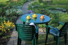 Les meubles de jardin parmi des fleurs s'approchent du chemin de jardin des dalles Photo stock