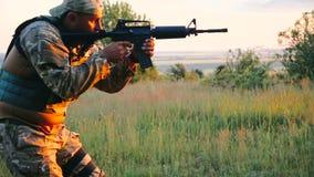 Les militaires visent sur l'ennemi avec l'automate dans la steppe banque de vidéos