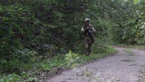 Les militaires vont sur l'offensive à l'encontre l'ennemi Un soldat dans des pousses d'un camouflage d'un fusil clips vidéos