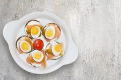 Les mini sandwichs avec du pain foncé avec les oeufs et le yaourt saumonés sur en céramique blanc plat Photographie stock