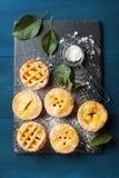 Les mini tartes aux pommes d'automne sur l'ardoise noire embarquent la vue supérieure Desserts savoureux de pâtisserie images libres de droits