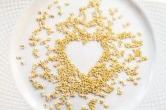 Les minuscules et les chiffres de pâtes chaotiques d'alphabet ont dispersé dans une forme de coeur Photos libres de droits