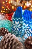 Les mitaines bleues avec le modèle de jacquard se tiennent dans la perspective des lumières de scintillement d'arbre de Noël Photo libre de droits