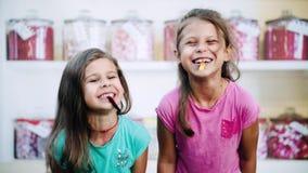 Les modèles drôles positifs rient et mangent la sucrerie clips vidéos