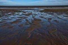 Les modèles faits dans le sable comme marée sort Image libre de droits