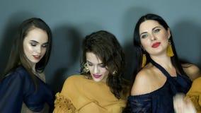 Les modèles heureux avec le maquillage chic dans des boucles d'oreille luxueuses sourient pendant la séance photos clips vidéos