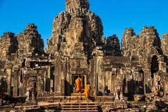 Les moines dans les visages en pierre antiques du temple de Bayon image libre de droits