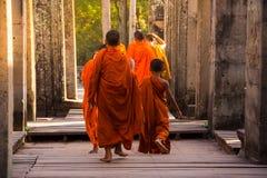 Les moines dans les visages en pierre antiques du temple de Bayon, Angkor image libre de droits