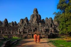 Les moines dans les visages en pierre antiques du temple de Bayon, Cambodge Photo libre de droits