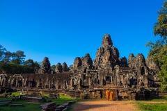 Les moines dans les visages en pierre antiques du temple de Bayon, Cambodge photos libres de droits