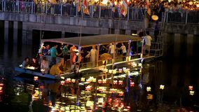 Les moines laissent tomber des lanternes sur la rivière pour la paix toutes les personnes dans la nuit