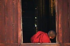 Les moines s'asseyent à la fenêtre photographie stock libre de droits