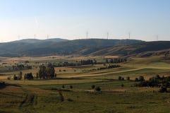 Les montagnes aménagent en parc avec un ciel nuageux bleu, moulins à vent photos stock