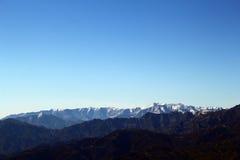 Les montagnes couvertes par neige éloignée Photo stock