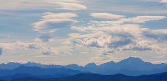 Les montagnes décrivent avec beaucoup de nuages photographie stock