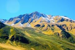 Les montagnes de Caucase en été, l'herbe verte sur des collines et la neige sur Chiukhebi font une pointe vue de village Juta, la Photos stock