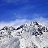 Les montagnes de neige en hiver exposent au soleil le jour et le ciel bleu avec des nuages Photographie stock libre de droits
