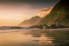 Les montagnes ont réfléchi sur le sable humide au coucher du soleil sur la plage images stock