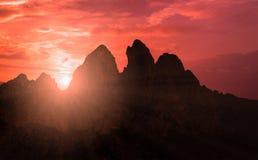 Les montagnes silhouettent à la scène de coucher du soleil avec la chute du soleil et rayonnent la lumière, nuages à l'arrière-pl Photos libres de droits