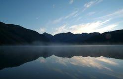 Les montagnes symétriques se sont reflétées dans le lac avec de beaux cieux bleus et brume dense Photos stock
