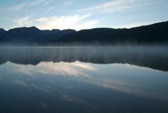 Les montagnes symétriques se sont reflétées dans le lac avec de beaux cieux bleus et brume dense Photographie stock