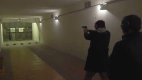 Les montres d'instructeur comme pousses d'homme d'une arme à feu dans la galerie de tir banque de vidéos