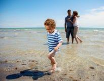 Les montres de couples comme fils marche à partir de l'eau Photographie stock