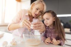 Les montres de fille en tant que sa grand-mère conduit l'oeuf dans la pâte pour un tarte fait maison Photos libres de droits