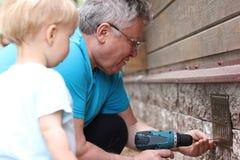 Les montres de petit-fils en tant que son grand-père fonctionne avec le tournevis Photographie stock
