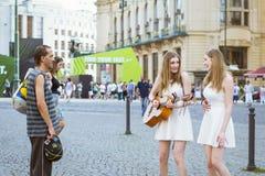 Les montres sans abri d'un homme en tant que deux fille-jumeaux chantent et jouent la guitare Images libres de droits