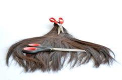 Les morceaux de cheveux ont coupé avec deux ciseaux rouges Photo stock