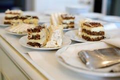 Les morceaux de coupe de gâteau des plats sur les nappes blanches Photos stock