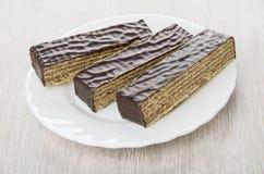 Les morceaux de gaufre de chocolat durcissent dans le plat blanc Photo stock