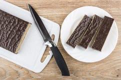 Les morceaux de gaufre de chocolat durcissent dans le plat blanc, planche à découper Image stock