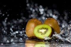 Les morceaux de kiwi avec de l'eau éclabousse et réflexion sur un CCB noir Photos libres de droits
