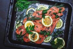Les morceaux de poissons rouges sur une casserole noire, décorés de la verdure et du citron, se ferment  image libre de droits