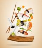 Les morceaux de sushi de vol ont servi du plat en bois, séparé sur le fond coloré Image libre de droits