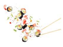 Les morceaux de sushi volent dans le ciel sur un fond blanc Images libres de droits