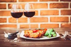 Les morceaux juteux de filet grillé de viande ont servi avec les tomates-cerises branche et la laitue d'un plat blanc, verre de v Photo libre de droits