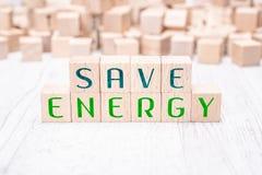 Les mots économiser de l'énergie constituée par les blocs en bois sur un Tableau blanc images libres de droits