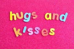 Les mots étreint et des baisers sur les lettres colorées Photographie stock libre de droits