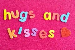 Les mots étreint et des baisers sur les lettres colorées Photos libres de droits