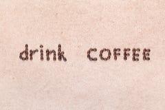 Les mots boivent du caf? ?crit avec des grains de caf?, tir d'en haut image libre de droits