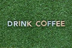 Les mots boivent du caf? fait ? partir des lettres multicolores sur le fond d'herbe, tir d'en haut, align? au centre photographie stock