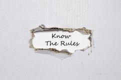 Les mots connaissent les règles apparaissant derrière le papier déchiré Photos libres de droits