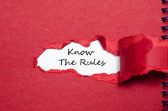 Les mots connaissent les règles apparaissant derrière le papier déchiré Photo stock