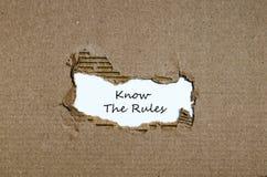 Les mots connaissent les règles apparaissant derrière le papier déchiré Image stock