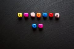 Les mots croient au texte sur les cubes en bois colorés, fond noir de pierre d'ardoise avec l'espace libre photographie stock