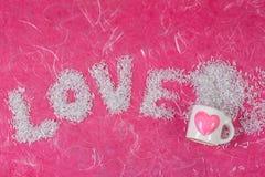 Les mots d'amour arrangent par la perle et le verre blanc avec la forme de coeur Images stock